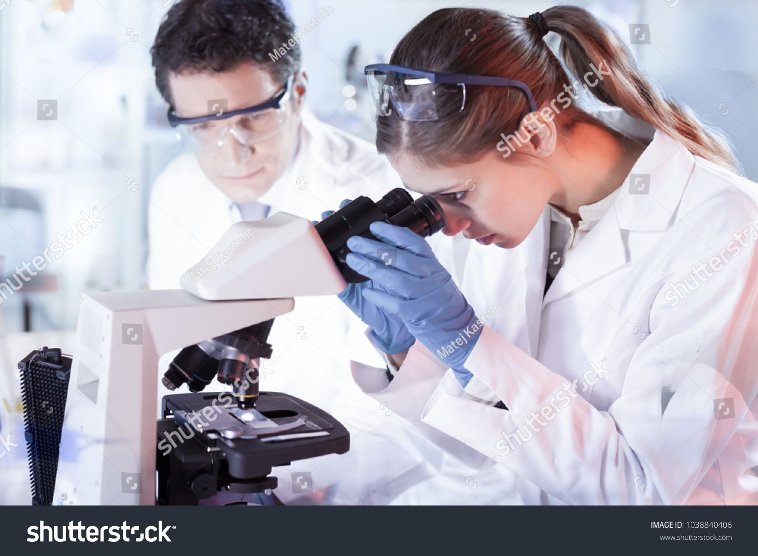 Life scientists researching in laboratory. Attractive
