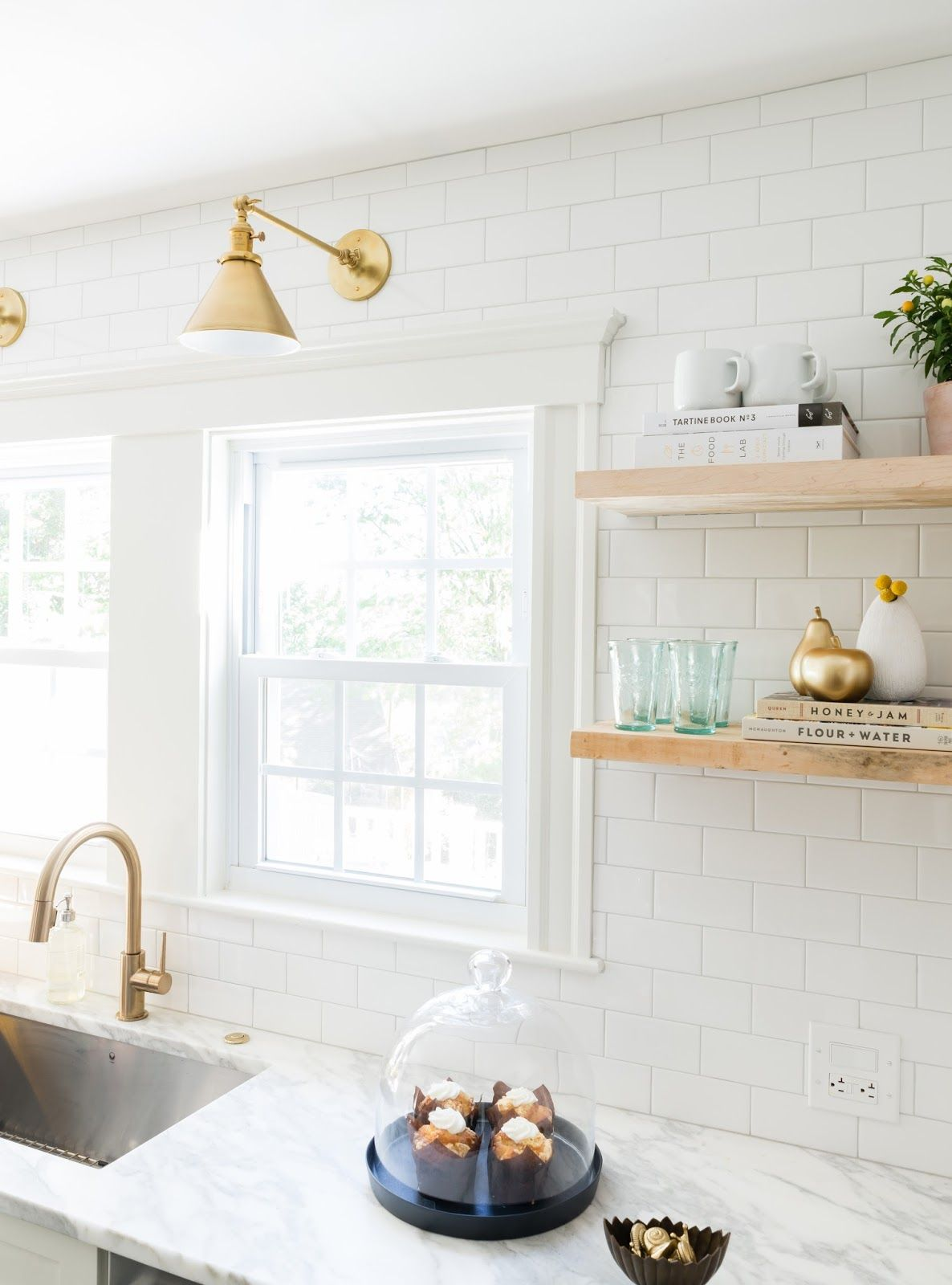 Pin by michelle cox rogers on b r i a r w o o d pinterest white and gold kitchen features white shaker cabinets adorned with brass pulls paired with calcutta marble countertops and a white subway tile backsplash dailygadgetfo Images