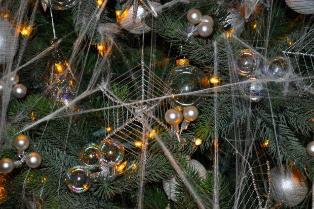 Christmas Traditions from Around the World UKRAINE PART 2   One Christmas morning, she awoke to find that spiders had trimmed her children's tree with their webs. When the morning sun shone on them, the webs turned to silver and gold.