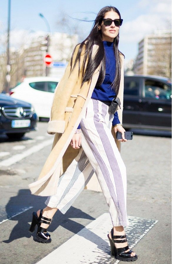 Gilda Ambrosio in pinstripe pants and a high neck blouse under a long camel coat