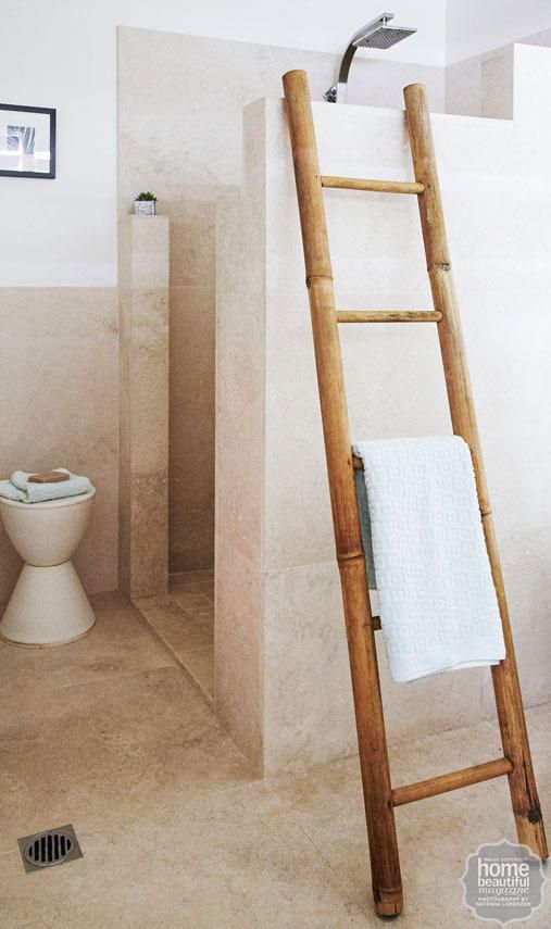 A walk-in shower clad in travertine tiles is a luxe addition, while a bamboo ladder brings an organic touch.