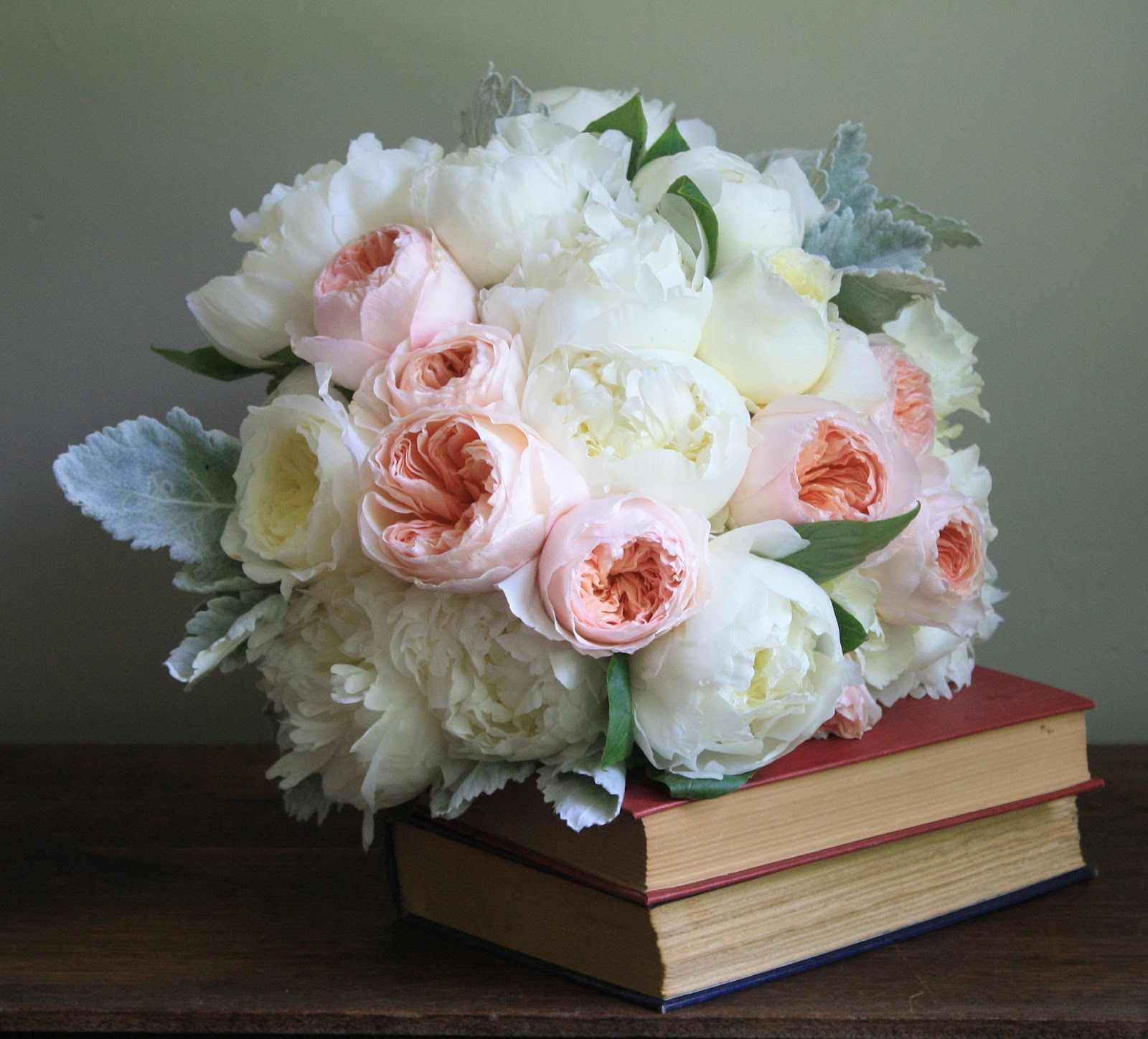The bridesmaids carried lush bouquets of coral charm peonies, hypericum berry, garden roses, and dusty miller.