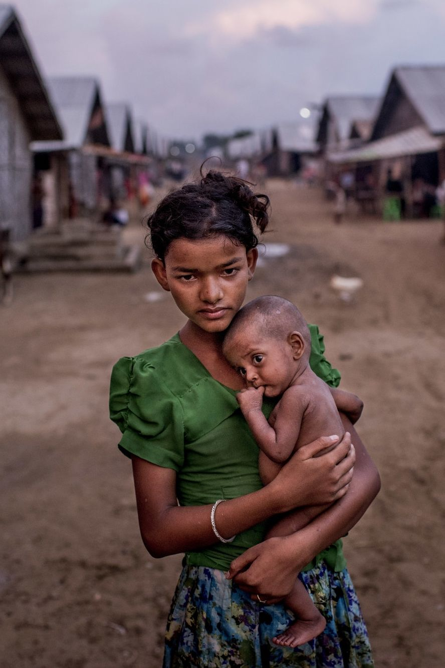 SITTWE, MYANMAR 6/5/2015 | A 12-year-old Rohingya girl held her undernourished brother in a squalid camp. Persecution forced thousands of Rohingya to flee the country. (Photo: Tomas Munita for The New York Times)