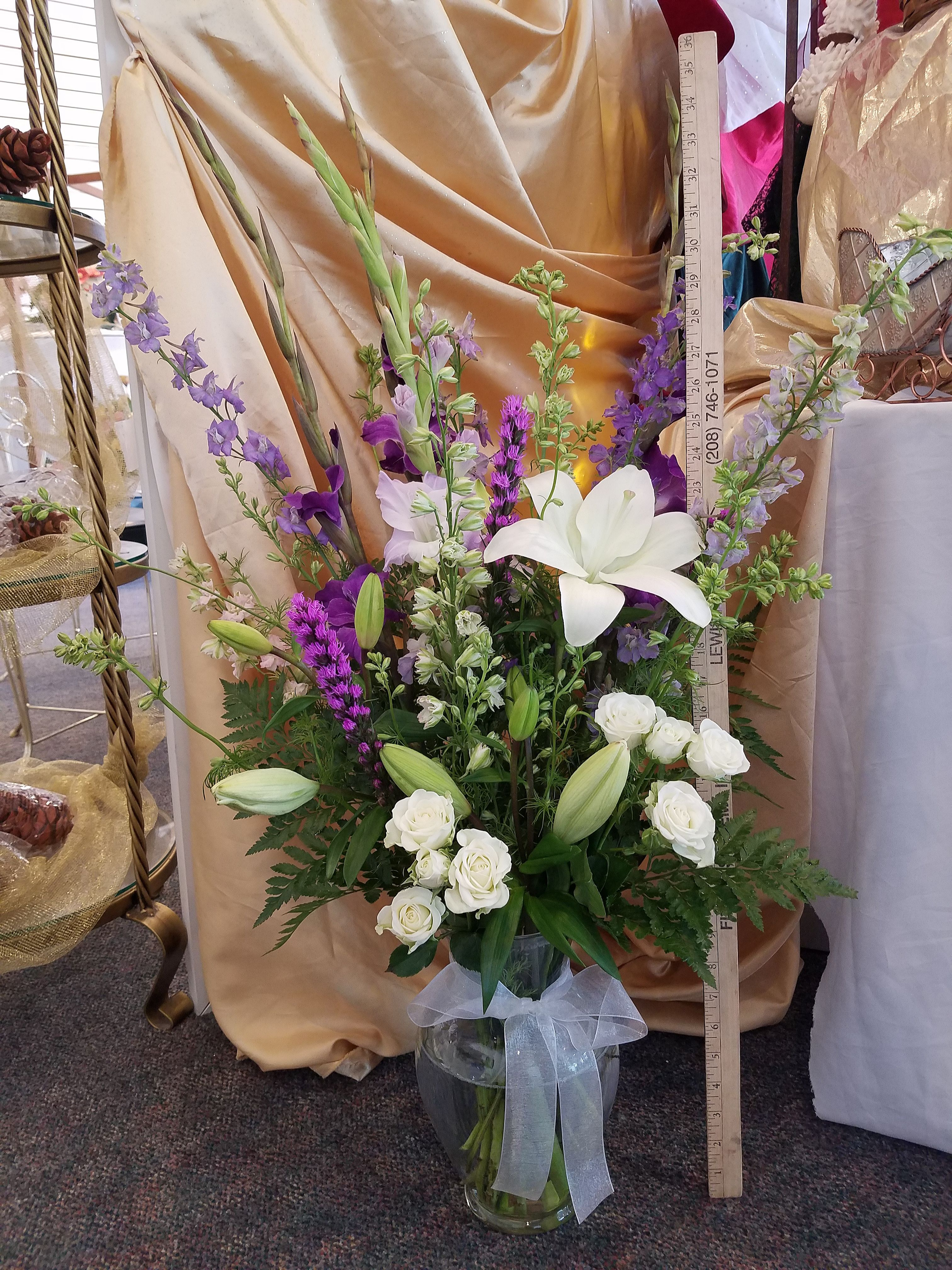 A tall vase in purples and whites with gladiolas, spray