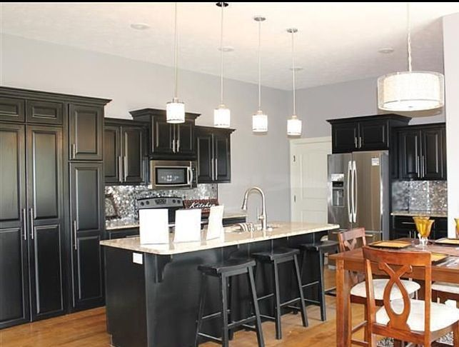 Black kitchen cabinets, granite top, and silver metallic ...