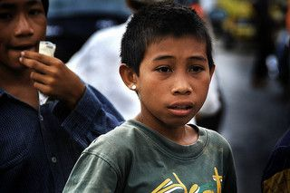 Children like these always roam the street in search for customers who may need them to carry their heavy load.  Makassarese kids are one of the most resilient children in Indonesia. Small in size but tough and show great endurance. Boys waiting for alighting customers from the public transport. Children like these always roam the street in search for customers who may need them for do everything in exchange of some roupies for survive.
