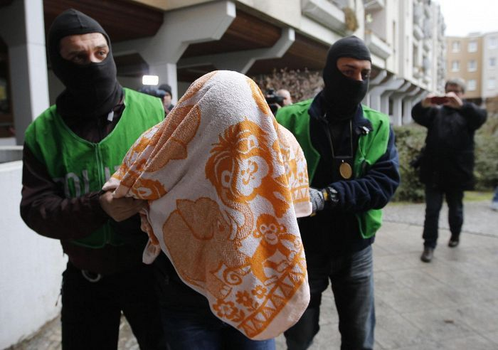 Poliisit taluttivat ratsiassa kiinni ottamaansa miestä, jota epäillään terroristiyhteyksistä, Kreuzbergin kaupunginosassa Berliinissä torstaina.