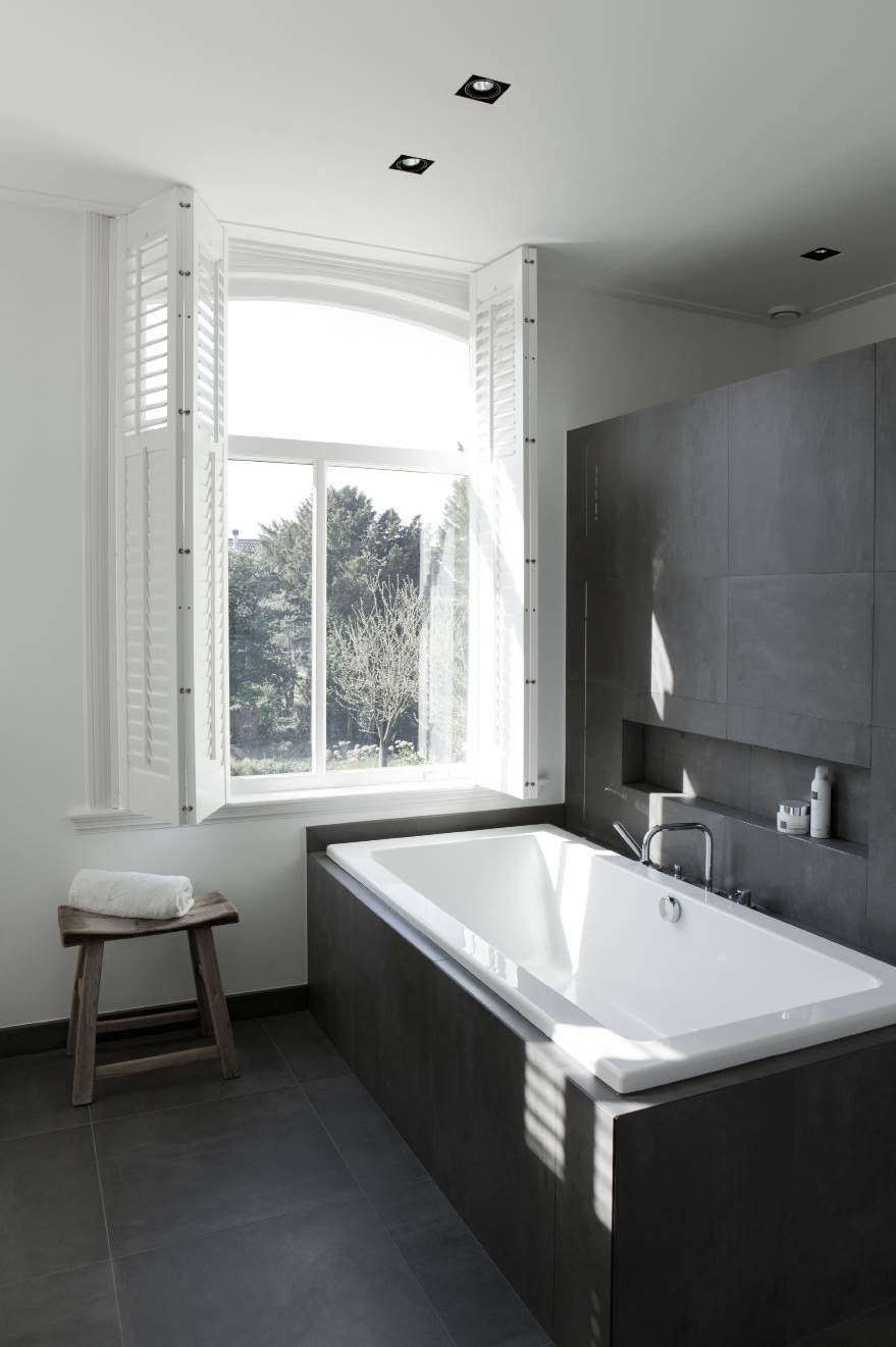 A BIG window and sparkling white tub perfectly offset the black ...