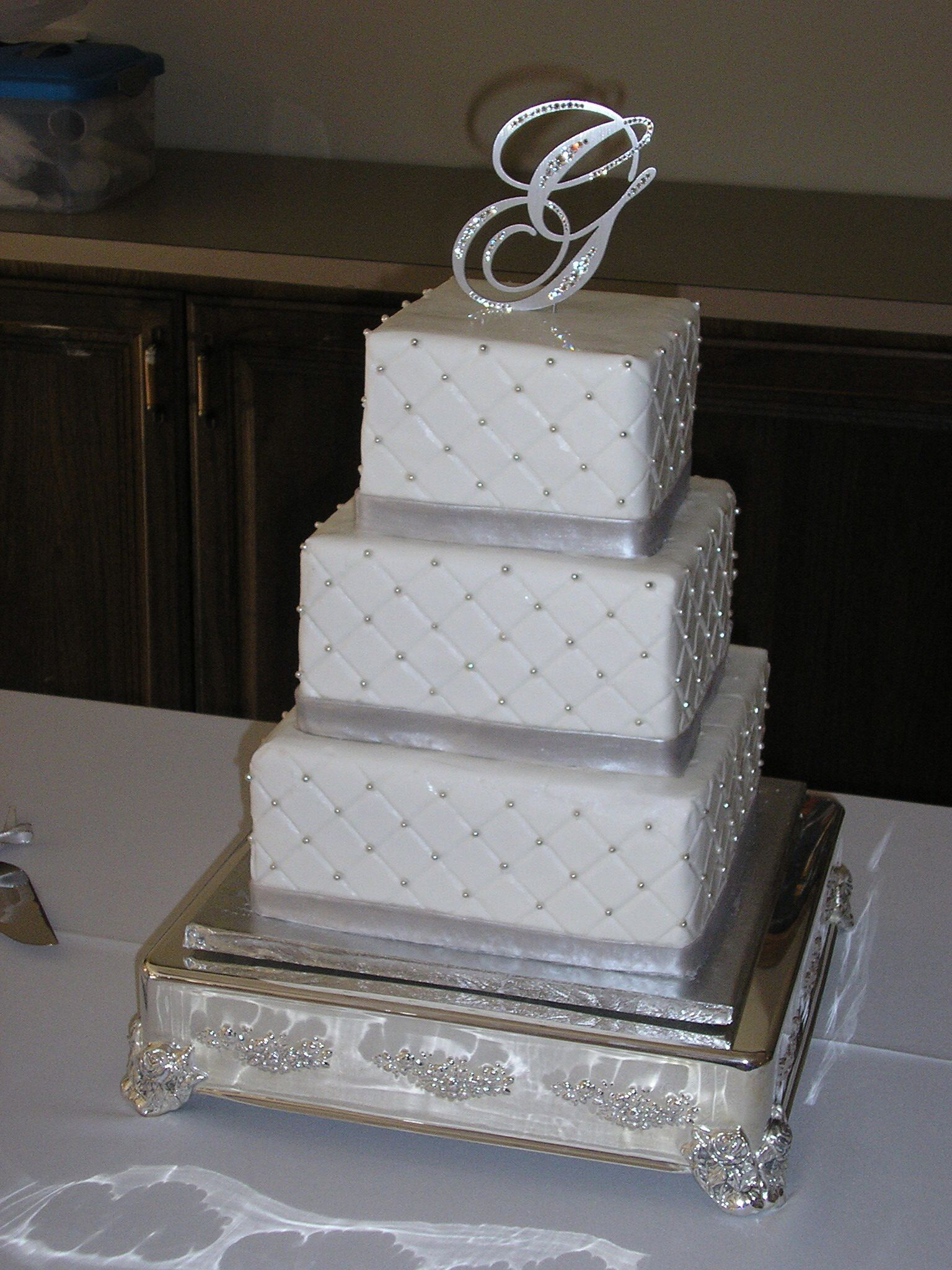 This tier square cake has a grid pattern with silver dragees on