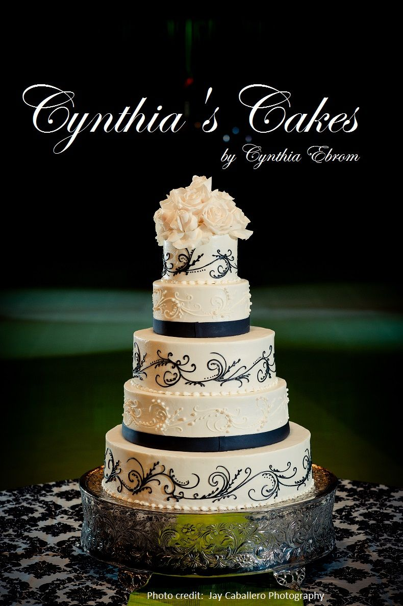 Wedding cake best described as regal black designs are etched onto