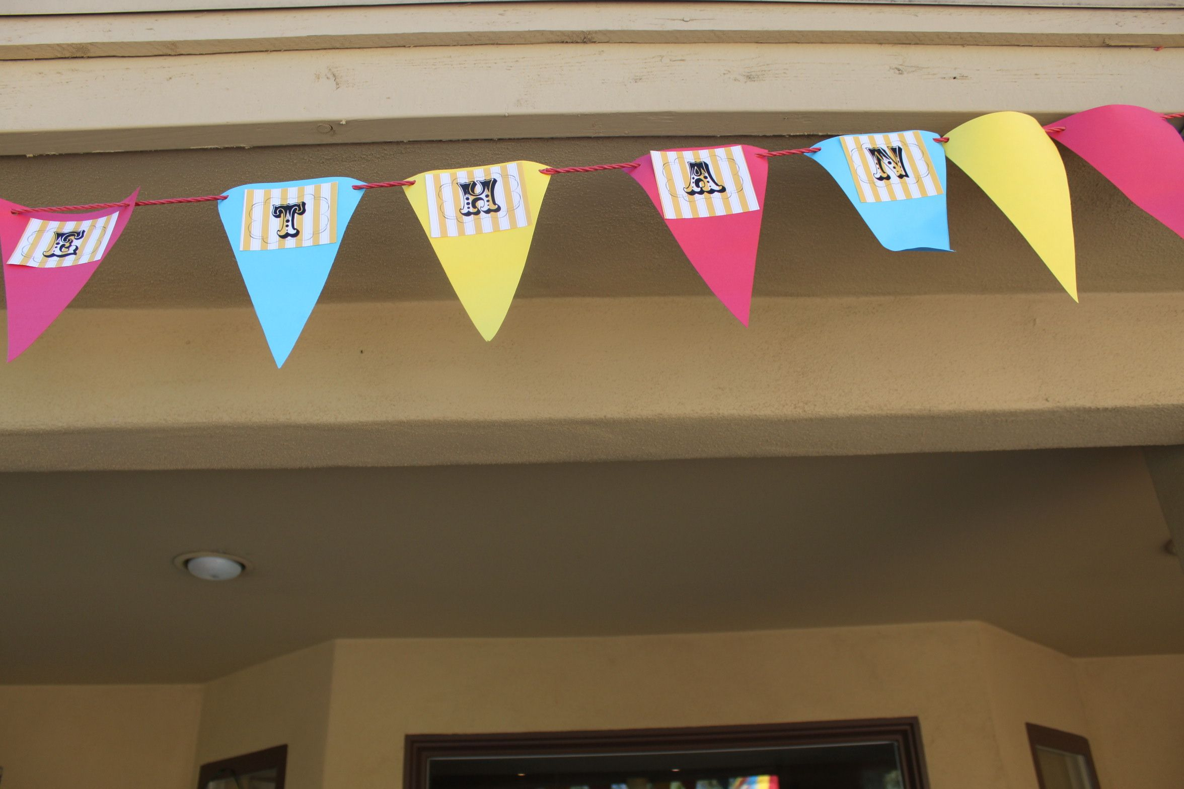 Customized birthday banner using red clothes line from dollar store and construction paper triangles.
