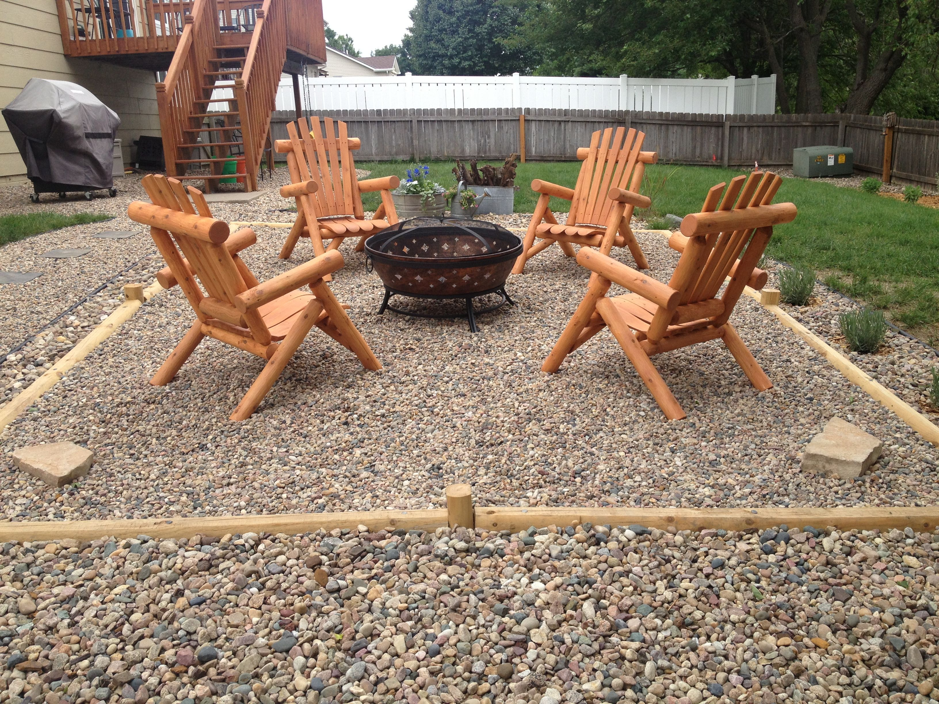 pea gravel fire pit with landscape timbers and cedar log