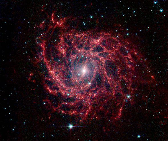 Looking like a spiders web swirled into a spiral, the galaxy IC 342 presents its delicate pattern of dust in this image from NASAs Spitzer Space Telescope. In the infrared the faint starlight gives way to the glowing bright patterns of dust found throughout the galaxys disk.