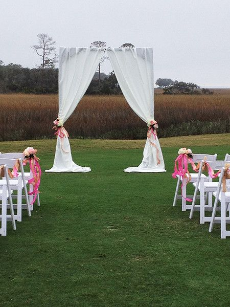 Open field ceremony with curtain vow exchange area in pinks. Wedding flowers created by Brooke Raulerson of Amelia Island Wedding Flowers, *An Artistic Florist Company. www.ameliaislandweddingflowers.com