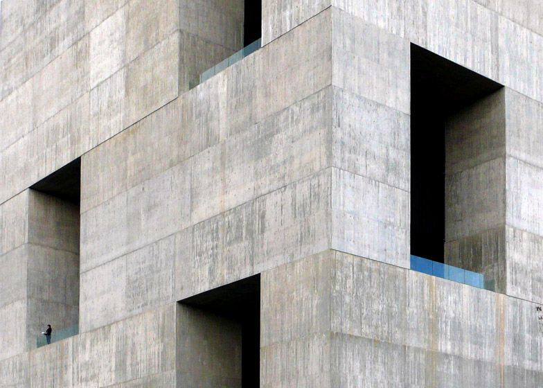 "Giant openings puncture this ""monolithic"" concrete innovation centre."