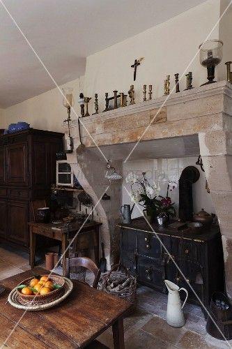Rustikale, Französische Küche Mit Antikem Holzherd In Ehemals Offenem  Kaminabzug; Im Vordergrund Schale Mit