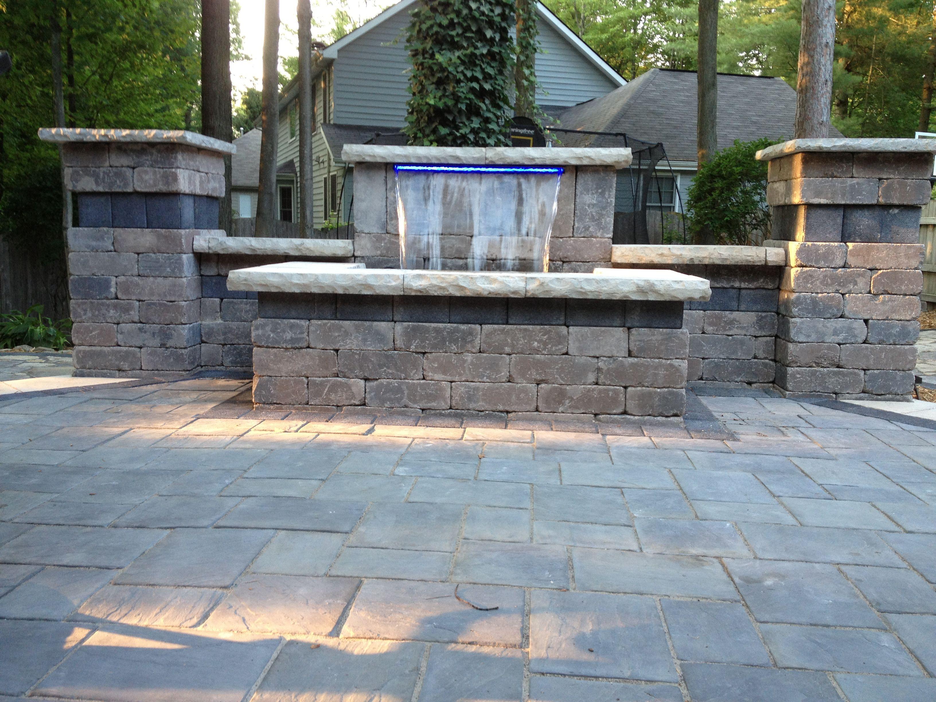 Beautiful waterfall and patio using Unilock brick pavers. Stonehenge  coping, Series 3000 black accent
