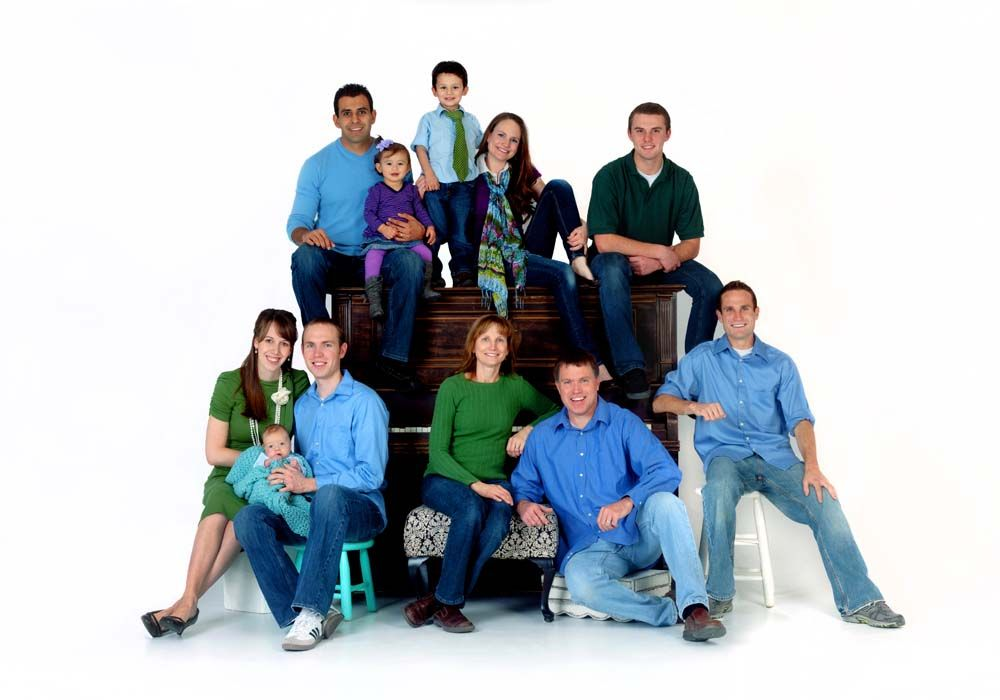 Using the piano to center this large family portrait is a great idea also the photographers use of many posing stools of different sizes is brilliant
