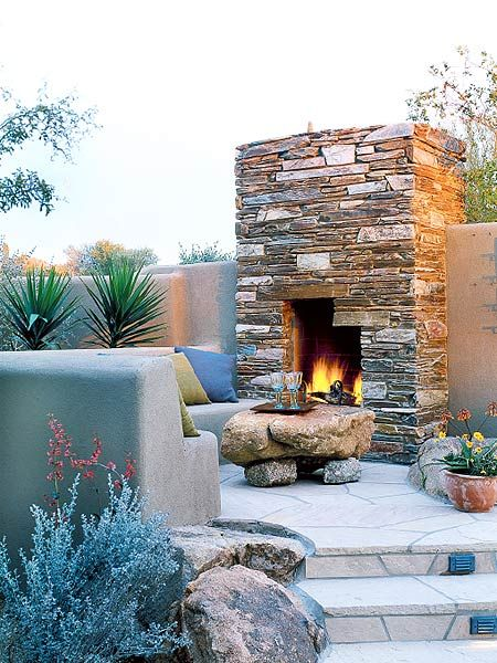 A curving seat wall defines an 8-foot-wide elevated patio in front of this distinctive stone fireplace (the stone is made of sedimentary clay from Arizona). Granite boulders edge the entrance and serve as a stationary coffee table. The fireplace is part of a stuccoed retaining wall set into a hill at the rear of the property. (Photo: Photo: Sunset)