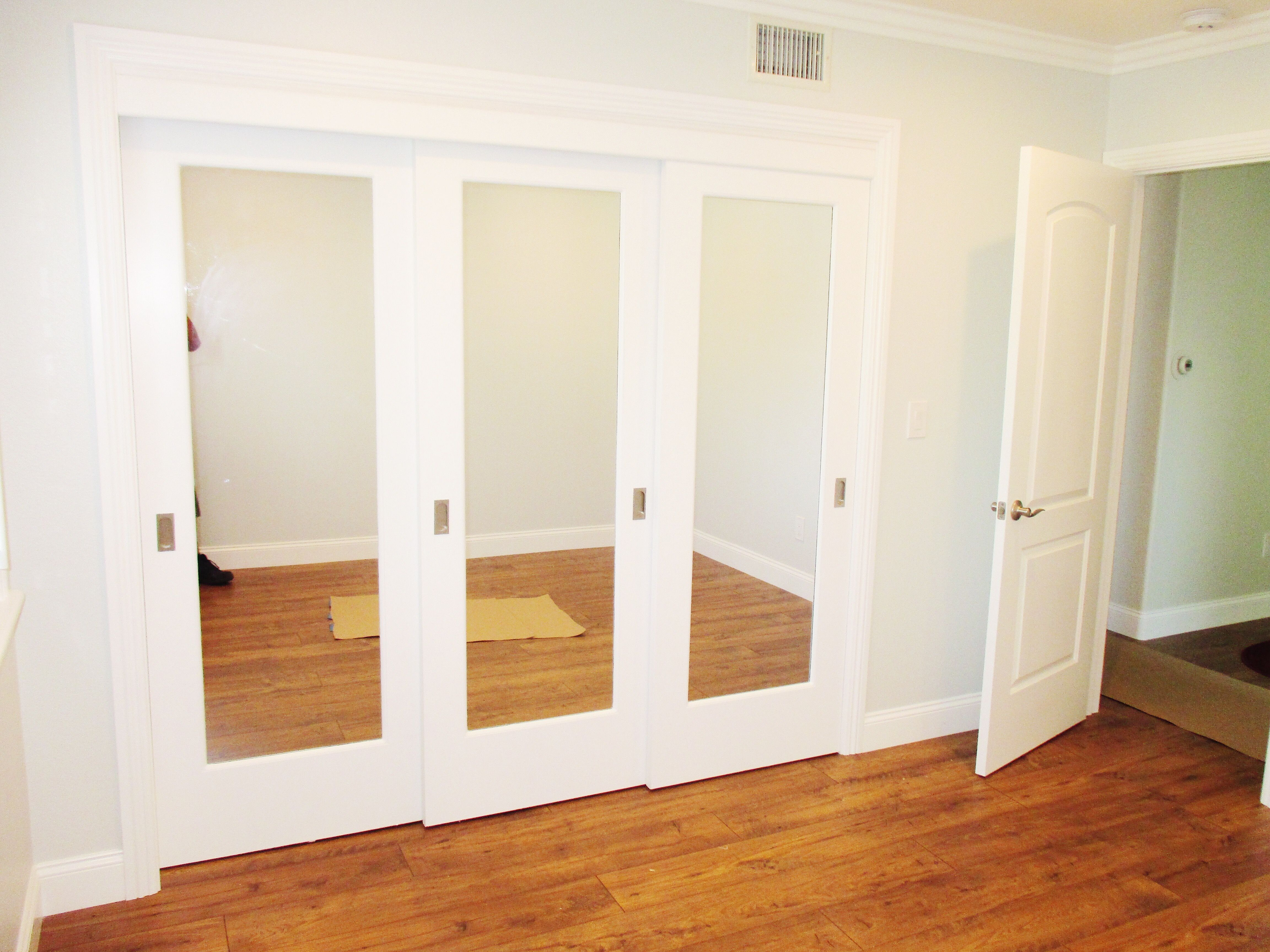 Do You Need Some Closet Doors But Want To Leave Your Floor Trackless Top Hung Doors Like These White 3 Pane Mirror Closet Doors Closet Doors Closet Apartment