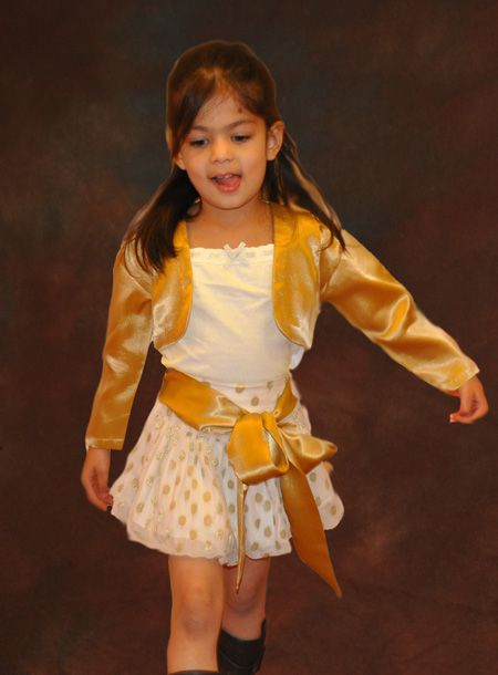 Gold polka dot Skirt A very beautiful stylish polka dot skirt for little girls.  Skirt curves in balloon shaped hem line at hem line Golden polka dot polyester fabric with underneath lining in polyester.  Waist belt in golden satin tied at front in a lovely bow.