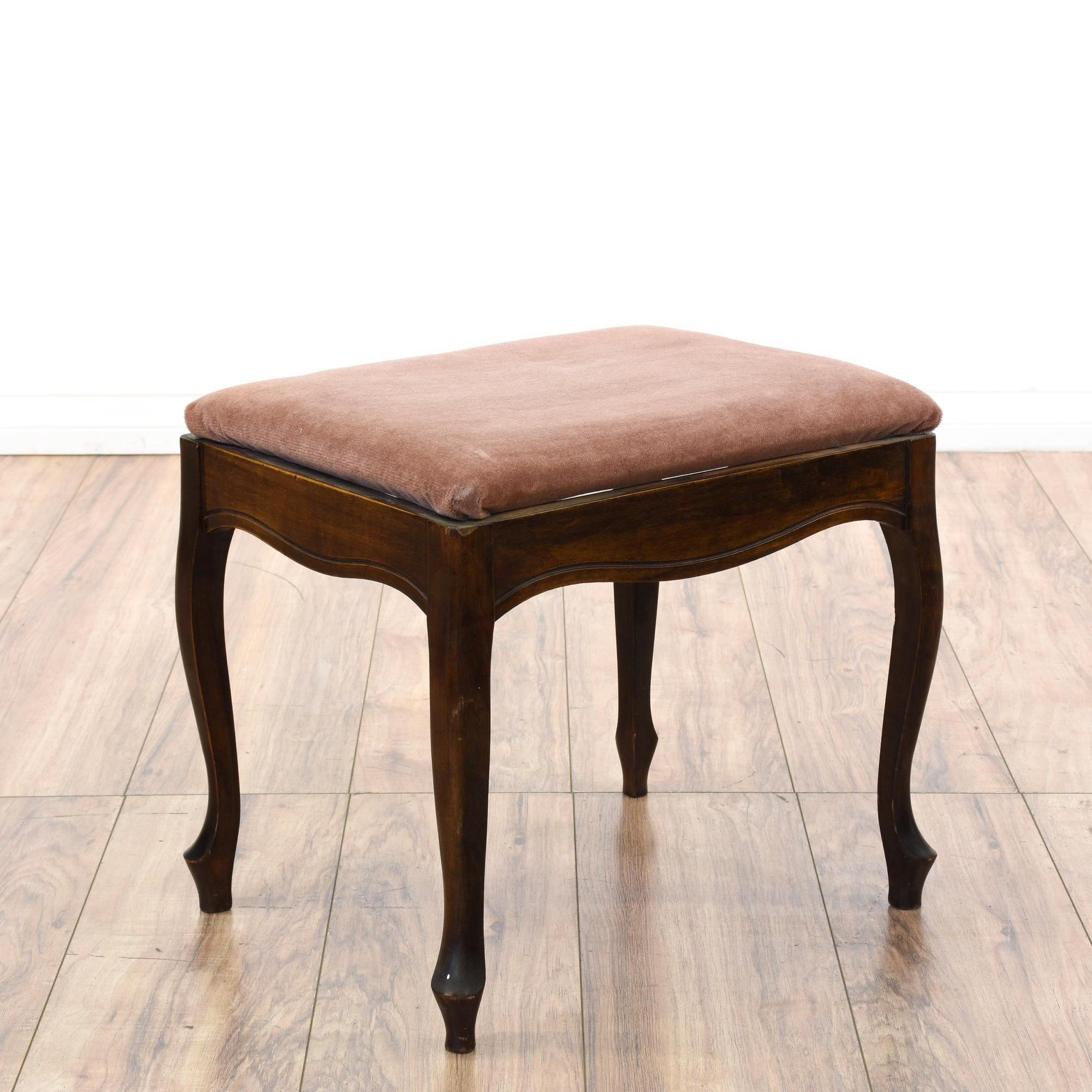 This vanity stool is featured in a solid wood with a glossy dark ...