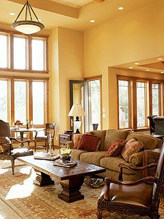 The great room has warm yellow colored walls and tall 18 for Living room with 9 foot ceilings