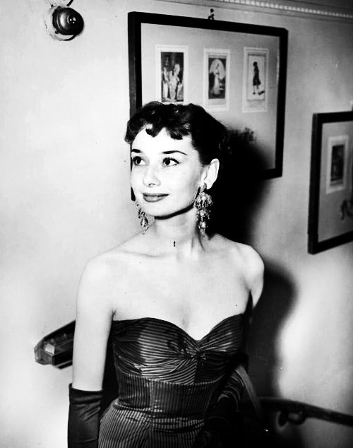 """Audrey Hepburn attends the Ambassadors Theatre in London's West End for the first night of """"For Love or Money"""". She is wearing 'Gold Chandeliers' - earrings of classical design, three tiered and with gold sequins."""