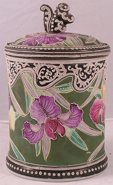 Circa 1890 Nippon Porcelain, Moriage Decorated  Humidor with Squirrel Finial. This fine piece of porcelain features a forest green backround and brightly colored flowers and is filled with typically exuberant moriage raised slip decoration and topped with a seated squirrel