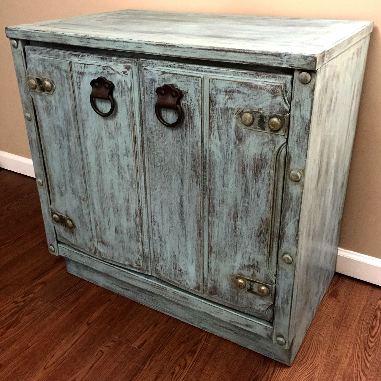 Distressed cabinet with interior shelf.  This small solid wood cabinet could be used as an end table, nightstand or tv/cabinet.  Painted in Persian Blue milk paint, waxed and distressed.
