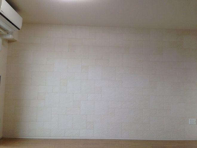 壁1面に石積み意匠のストーン ベージュ リビングルーム 施工例