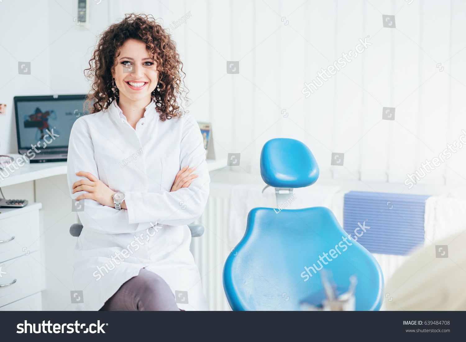 Portrait of female dentist. She standing at her office and