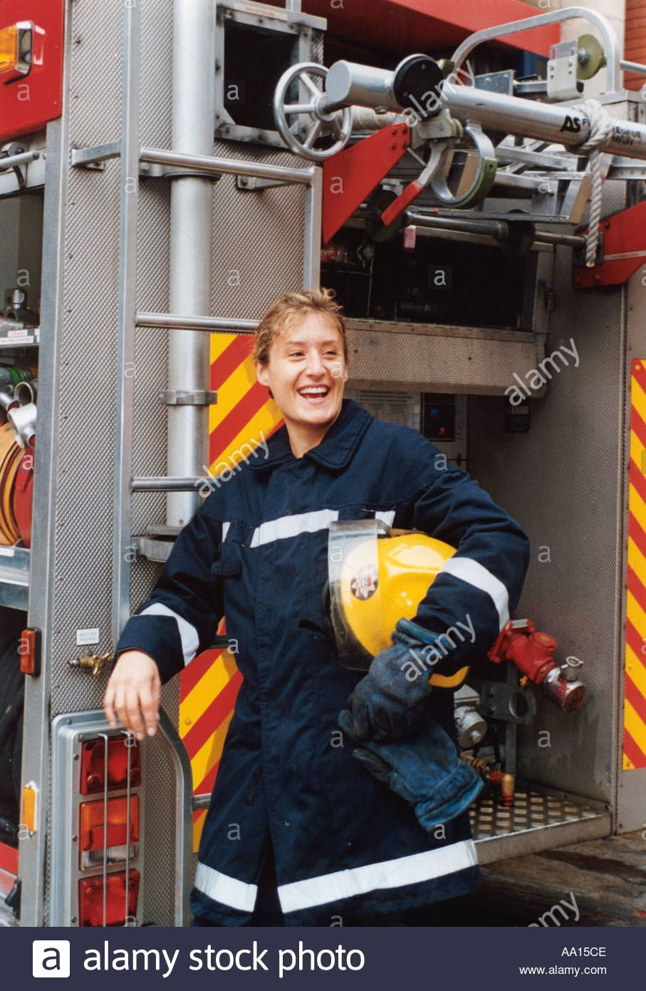 Female firefighter standing next to fire engine in uniform