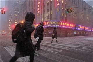 Image: Pedestrians walk through blowing snow in front of Radio City Music Hall.. Thursday, .02-09-17 it was 68 degrees on Wednesday~