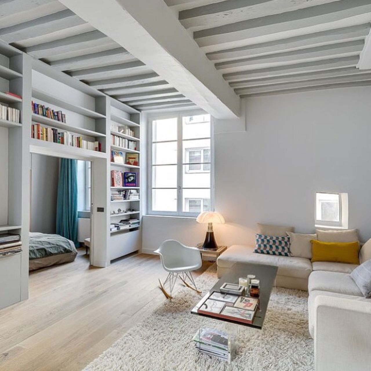 Living room with white wood beams and wood floors