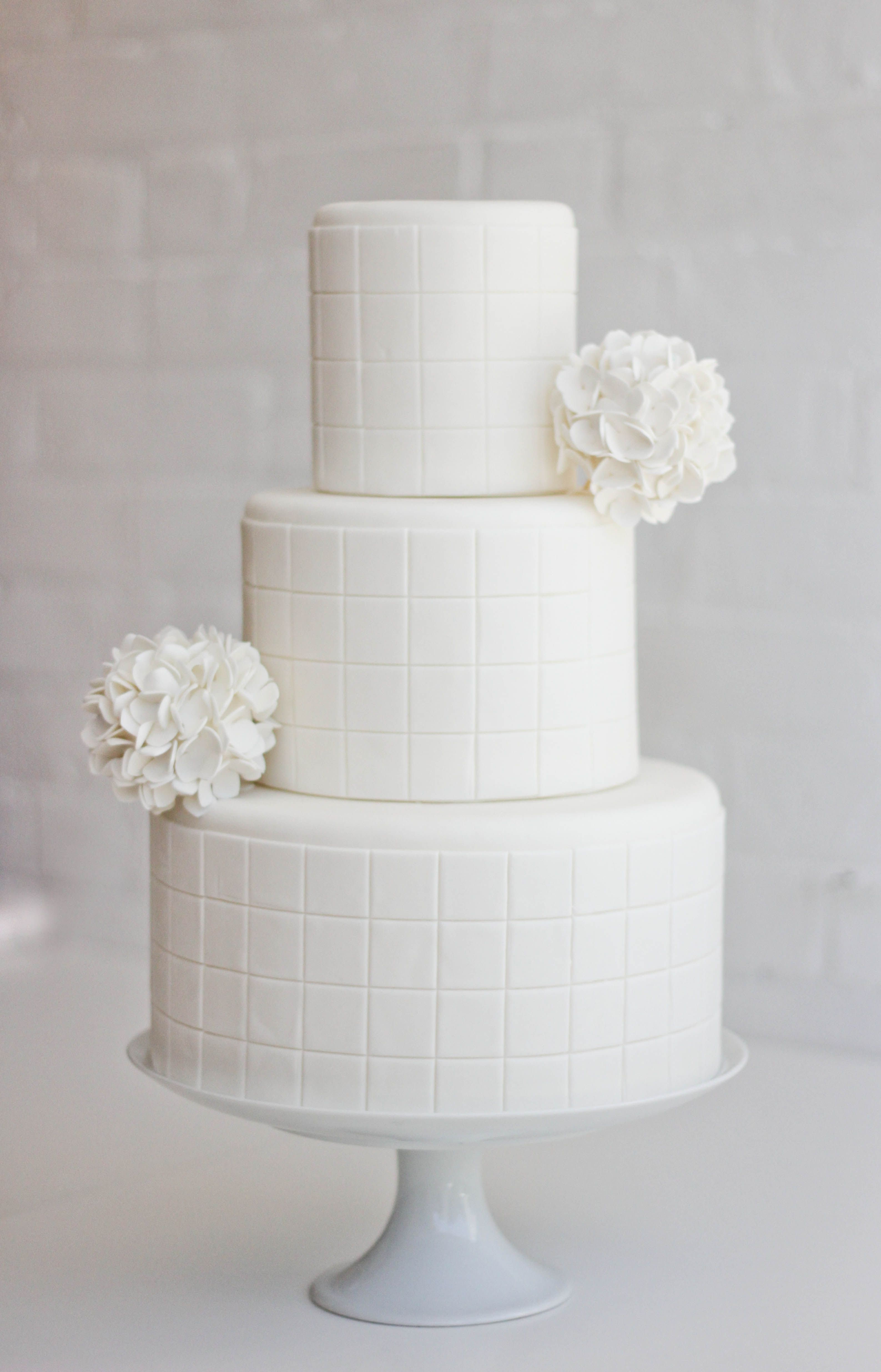 Gorgeous white squares design wedding cake with flowers we