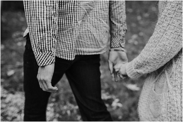 Autumn New Forest engagement shoot black and white of couple holding hands walking in woods