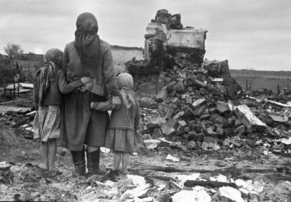 Russian mother and children looking at a destroyed home (1943)