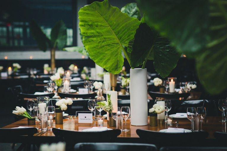 tiki tropical ... A tall, focal point arrangement helps with that because it means other centerpieces aren't blocking people's faces. That's one reason we love these elephant ears in a sleek white cylinder vase—chic and conversation-friendly! #weddingpreparationmarriage #elephantearsandtropicals