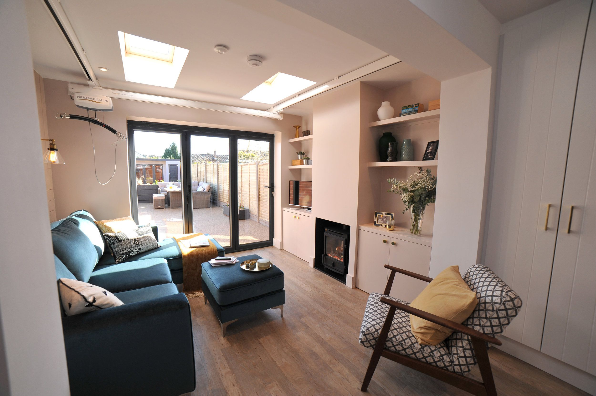 Blush pink living room with anthracite bifold doors, a