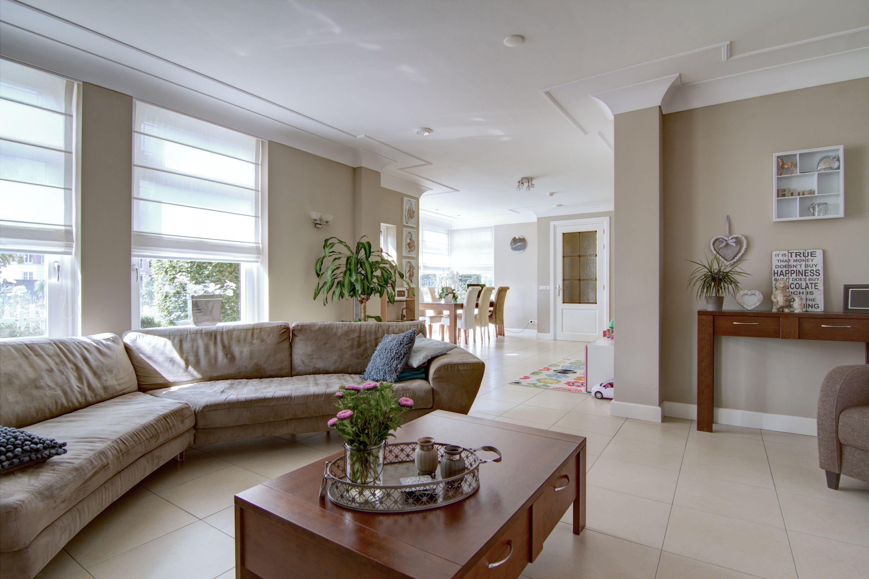 De sfeervolle woonkamer is verdeeld in een zit- en een royaal ...