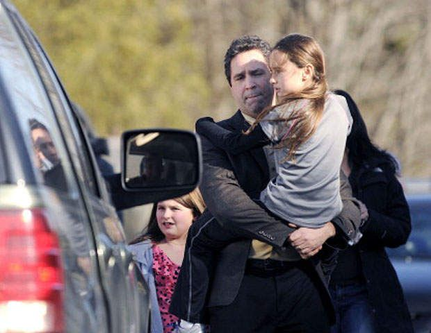 Parents carry their children as they leave Sandy Hook Elementary School in Newtown, Connecticut, Friday, December 14, 2012 (John Woike/Hartford Courant/MCT via Getty Images)