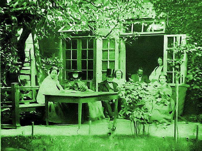 H.C. Andersen og familien Collin. Man har sat sig til fotografering i gården ud mod Store Strandstræde under det store lindetræ