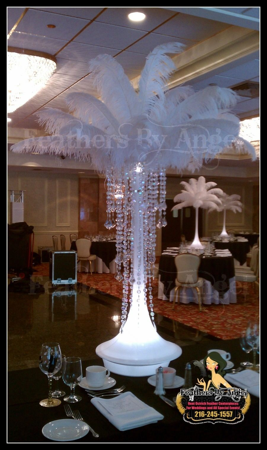 Ostrich feather centerpieces add hanging crystals from