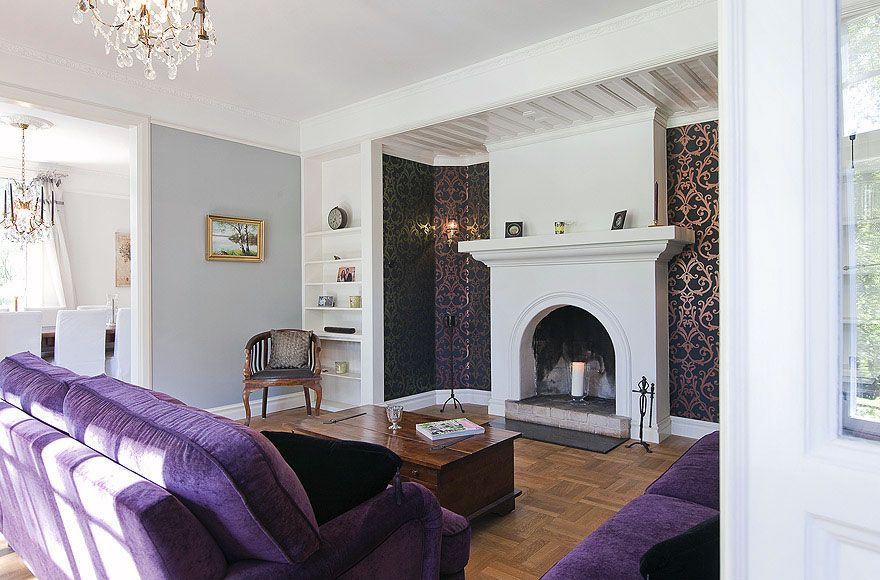 Warm Living Room With Purple Sofa And Fireplace Mantels Living