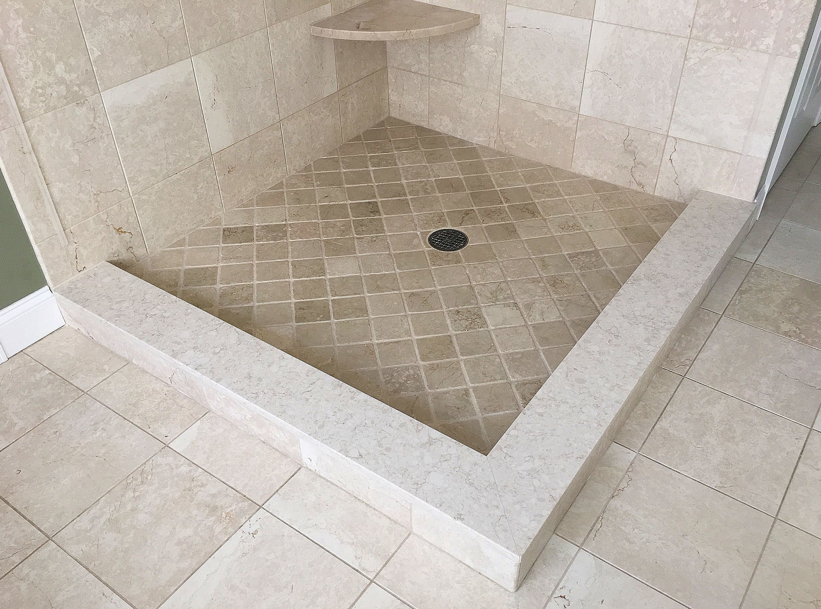 Traditional Botticino marble shower & floor tile with an