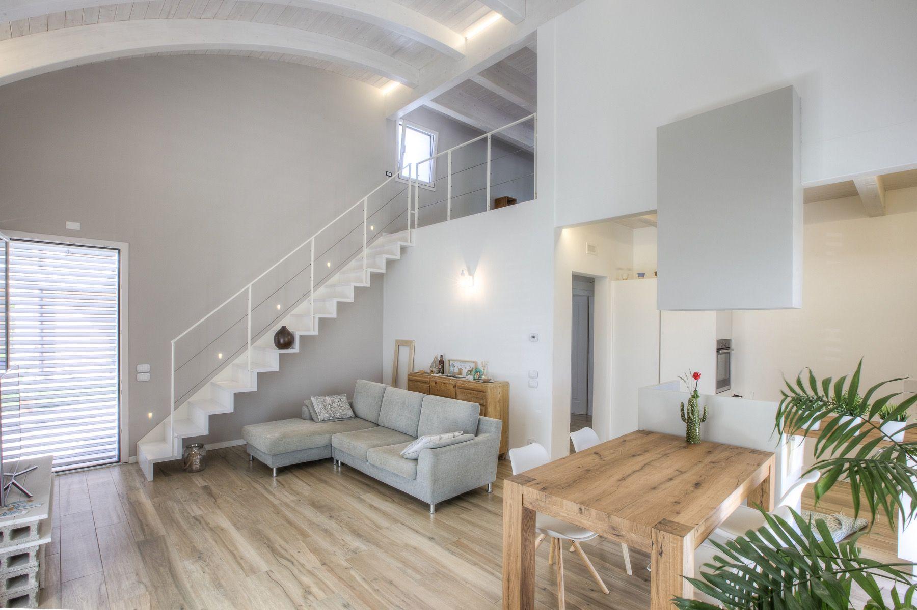Lo splendido open space che ospita cucina e soggiorno, con le scale ...