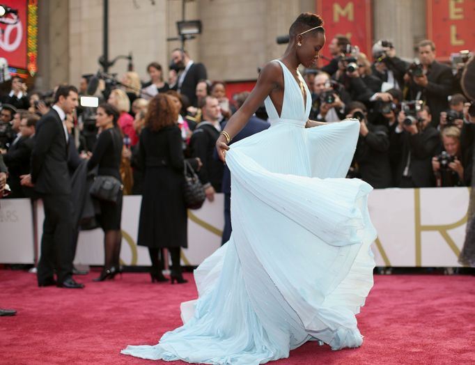Lupita Nyong'o, who's taken the fashion world by storm, takes a twirl on the Oscar red carpet in an ice blue Prada gown.