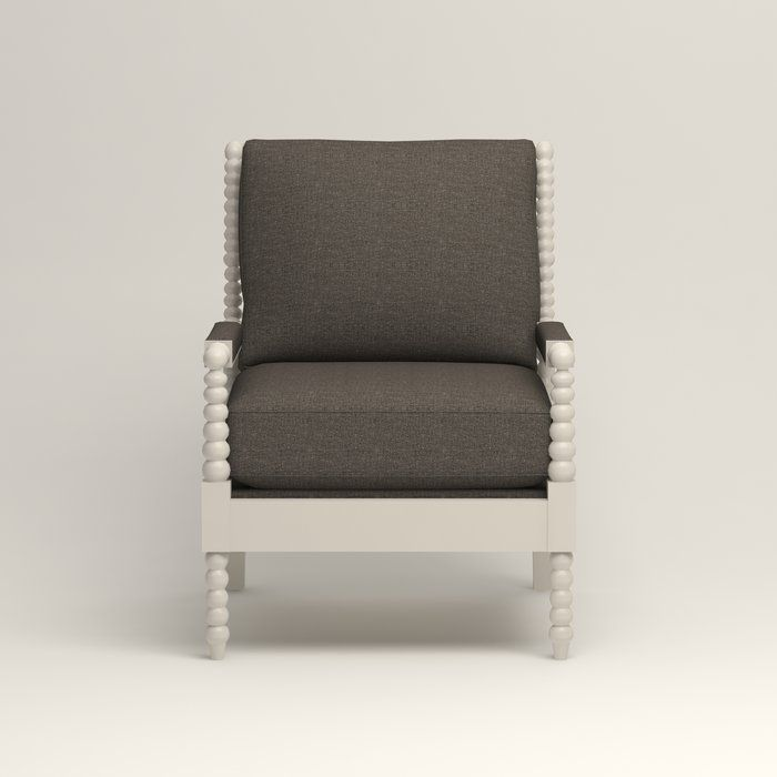 This vintage-style chair features padded armrests, welted seat and back cushions, and a spooled wooden frame.
