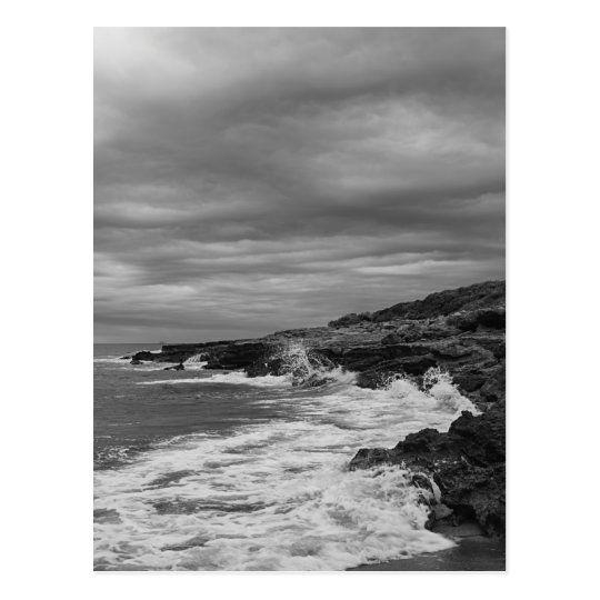 Postal de un paisaje costero con las olas chocando contra las rocas
